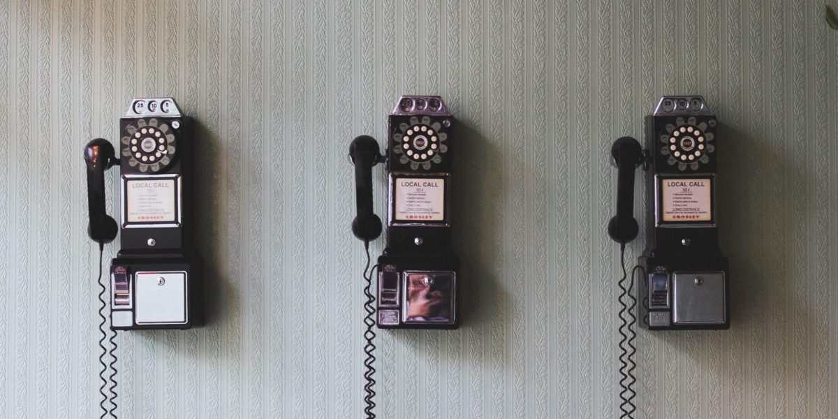 3 rotary pay phones hang on a white wall