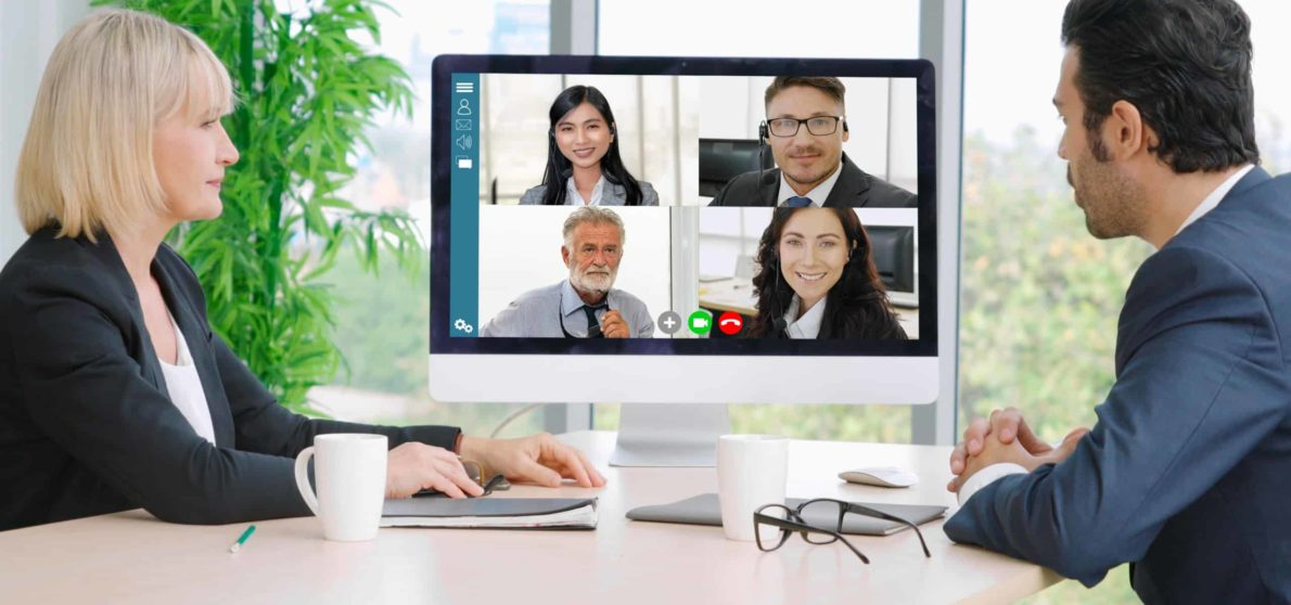 A female and a male manager meet in person while video conferencing their team members.